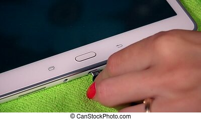 hand attach cable to tablet computer device on green background