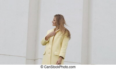 Happy girl with long hair in coat posing on the background. Slowly