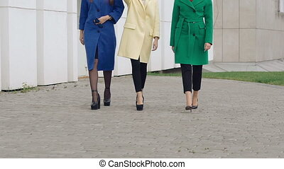 Three happy women walks runway in cashmere wool coats on the...