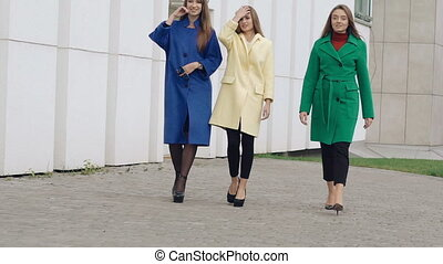 Three assured women walks runway in cashmere wool coats on...