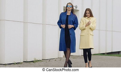 Two assured women walks runway in cashmere wool coats on the...