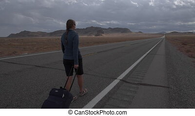 Young woman with a suitcase walking down an empty road