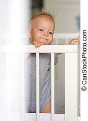 Baby boy standing in crib - Baby boy with blue eyes standing...