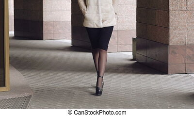 Passionate woman in furry coat walks in front of camera. Slowly