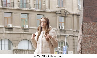 Stylish woman in furry coat walks runway and posing on the...