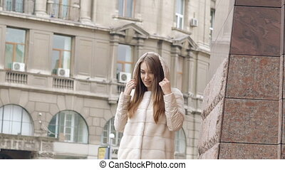 Stylish woman in furry coat passes, smiles and wears hood on...