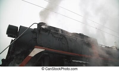 old black locomotive. steam smoking in real time. Winter...