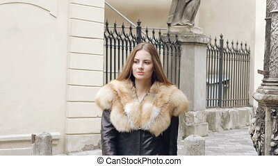 Cute girl posing in furry jacket and smiling on the street....