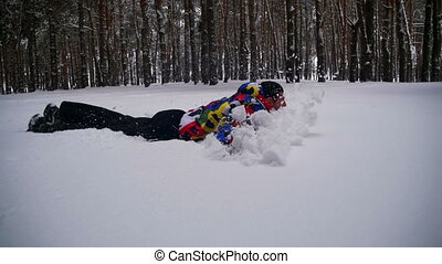 Happy Man Dives into the Deep Snow and Having Fun in the...