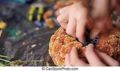 Close up view of hands making basket of flowers. It is...