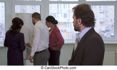 Middle aged businessman looks at his partners - Middle aged...