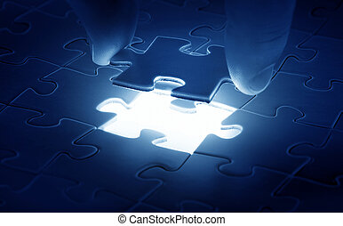 Hands placing last piece of a Puzzle