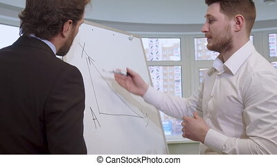Businessman draws on the flip chart - Attractive young...