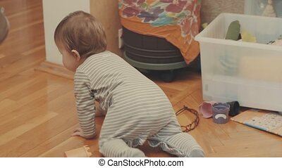 Little baby girl crawling on the floor, then turning around the corner