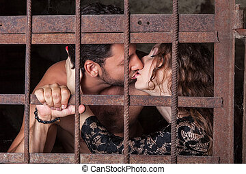 Young couple kissing behind bars