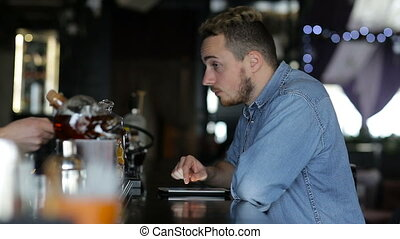 A young man uses tablet and drink coffee while sitting at the bar