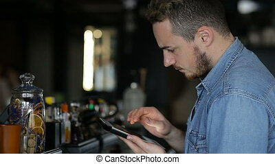 A man uses tablet while sitting at the bar