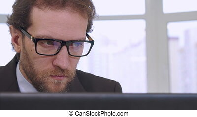 Businessman looking at laptop screen - Caucasian bearded...