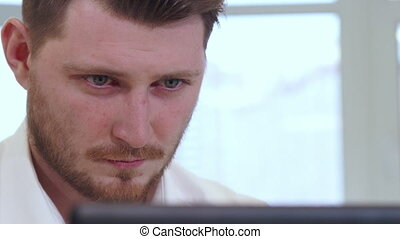 Male manager works on computer - Young attractive male...