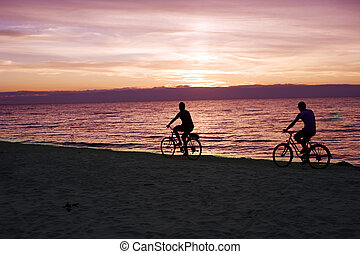 Bicyclists on the beach - Two people rides by bicycles on...