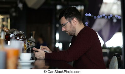 A young man uses tablet while sitting at the bar