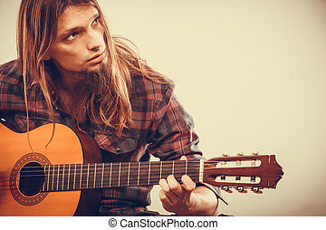 Boy with guitar. - Young long haired guy playing guitar....