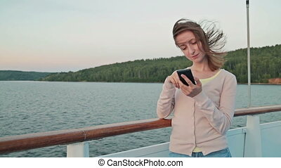 Woman using mobile phone on cruise ship
