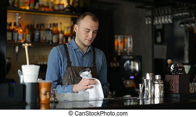 The bartender wiping glasses behind the bar