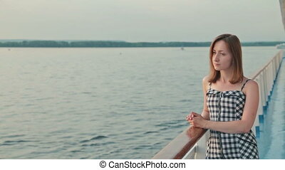 Young woman standing on deck of cruise ship