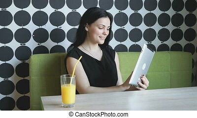 Girl watches photos using a silver computer tablet during...