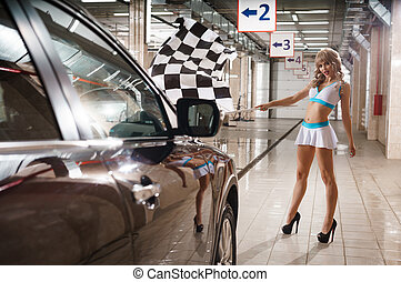 Full length of model with race flag at car wash - Hot leggy...