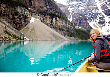 Woman Canoeing Portrait - A woman canoeing on Moraine Lake,...