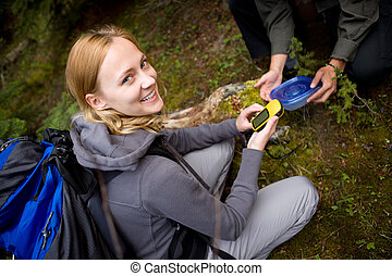 Geocache - A young woman finding a geocache in the forest