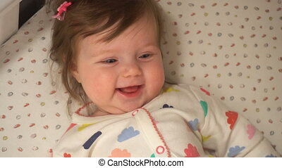 Cute baby girl smiling on the bed at home