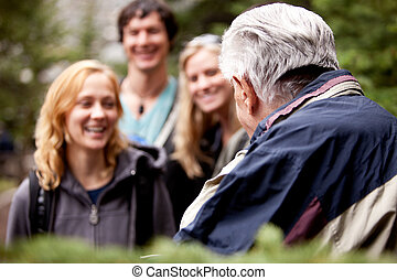 Elderly Hiking Guide - An elderly man talking to a group of...