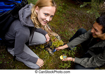 Geocaching - A young man and woman finding a geocache hidden...