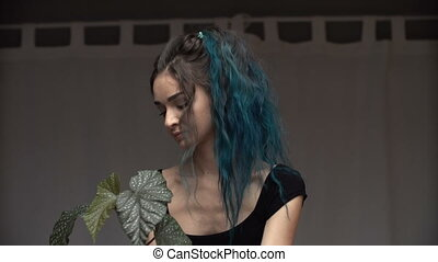Beautiful cute girl with dyed blue hair carefully transplant...