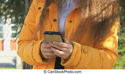 The attractive girl holding a mobile phone in the park