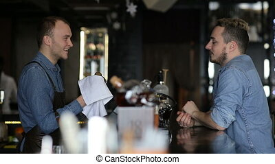 The bartender is a conversation with a young man in a bar