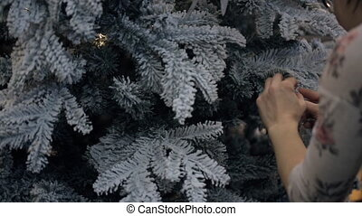 Asian woman hang first toy on pine tree in house. Merry...
