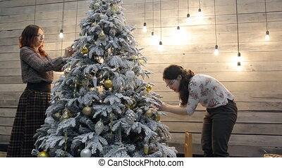 Two women friends decorating Christmas tree at home. Females...