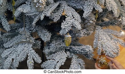 Checking decoration on artificial fir tree covered with frost.