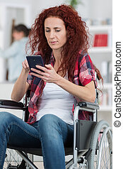 handicapped redhead woman texting and surfing on her...