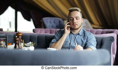 Lonely young man talking on the phone in restaurant.