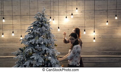 Women decorate white green Christmas tree with toys in...