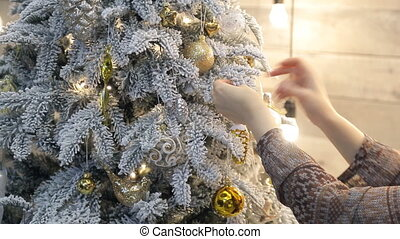 Somebody tie gold ribbon from organza as decoration to Christmas tree.