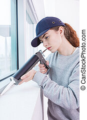 Woman using caulking gun