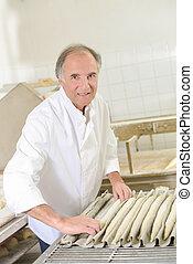 Baker rolling dough into baguettes