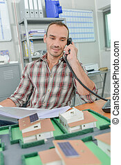 Man on telephone, model houses in front of him
