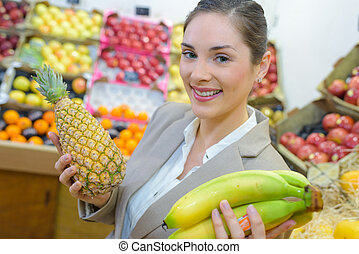 pretty woman buying fresh fruits and vegetables at...